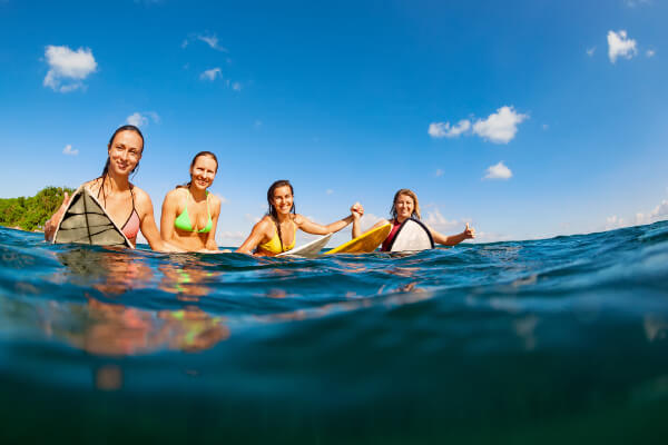 4 friends sitting on their surf boards in the water
