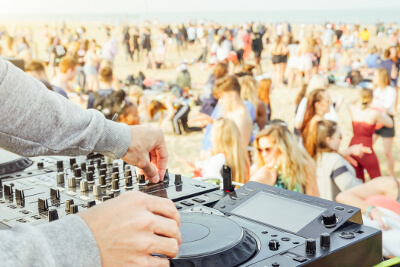 dj working on turntable with crowd in the background