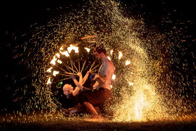 two fire twirlers in the middle of a show