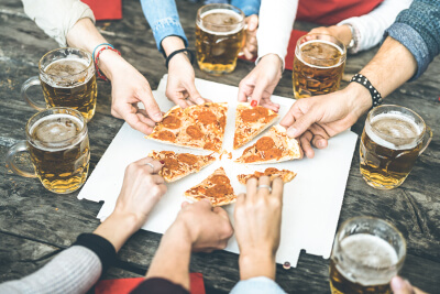 friends eating pizza and drinking