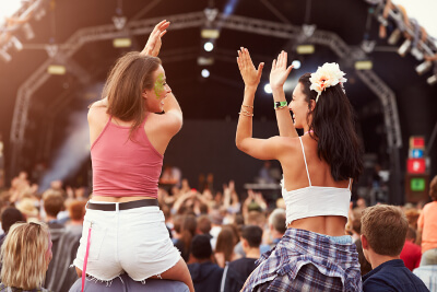 two girls sitting on men's shoulders at a concert
