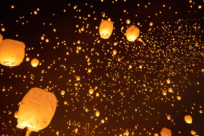 glowing lanterns floating in the night sky